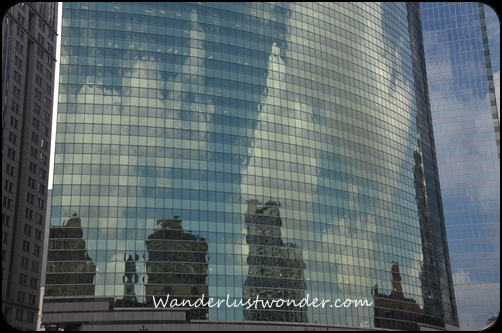 Clouds and other buildings reflected.