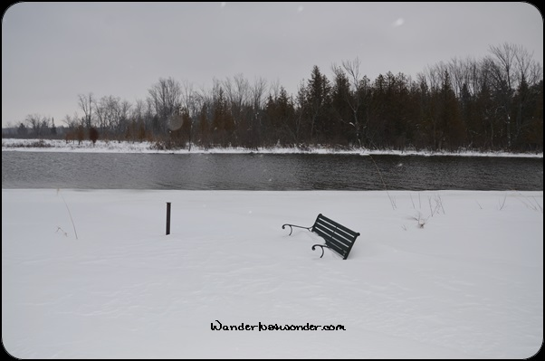 Bench buried in the snow.